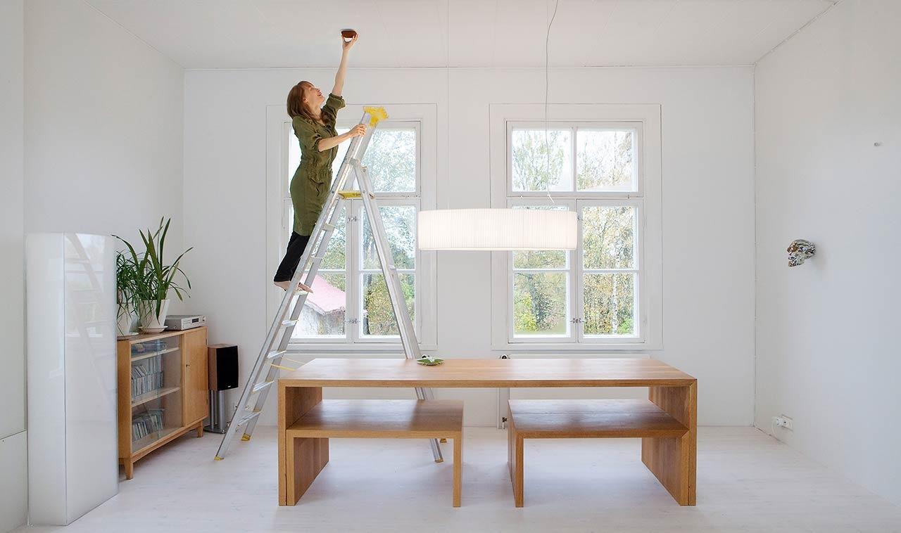 Woman installing Jalo Helsinki smoke alarm in a house